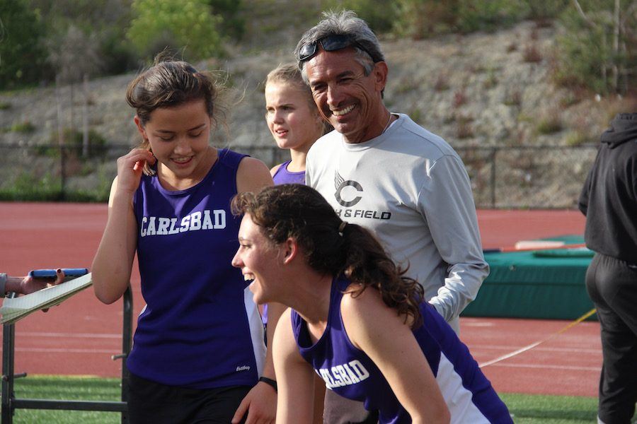 Coach+Manny+congratulates+senior+Sam+Schneider+as+she+finishes+the+4X400+relay+race+at+Sage+Creek