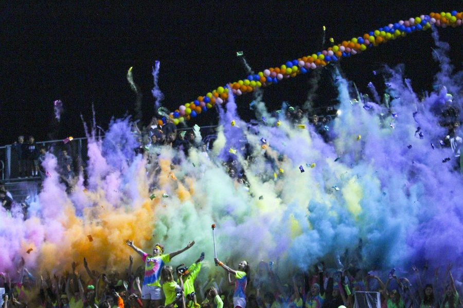 Loud crowd throws neon powder up to celebrate last home game. Varsity football wins their last home game before CIF finals 48-44.