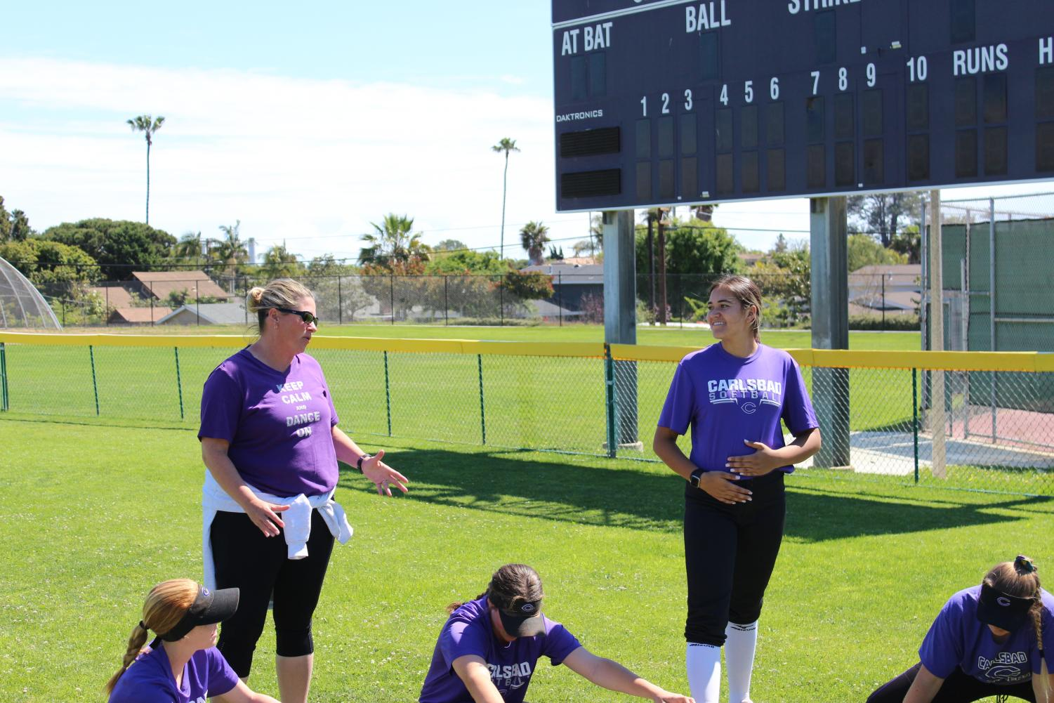 Mrs. Waters (left) gives her team a pep talk while they stretch before their 2-hour practice. Senior Alanna Nelson-Thiede (right) listens intently.