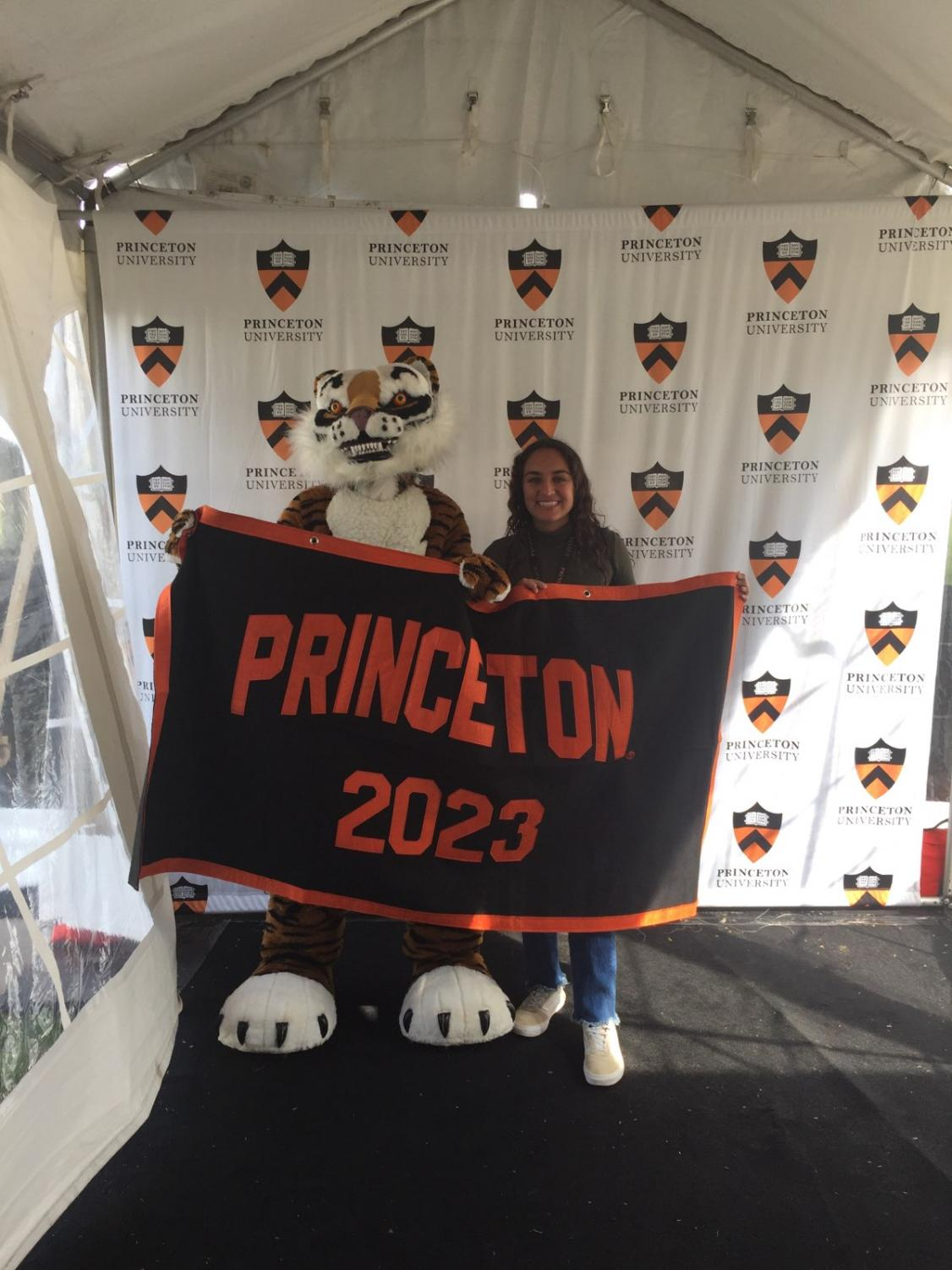 Kulchar poses with the Princeton tiger, holding up a Princeton class of 2023 banner.