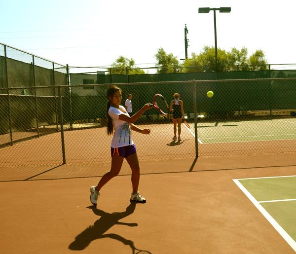 Freshmen Miranda Tomaneng struts for the ball as she uses her skills in tennis performing a forehand.