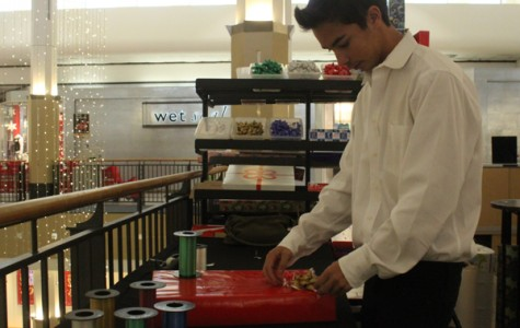 Senior Andrew Lopez wraps presents at the Plaza Camino Real mall on Dec. 14. Lopez and fellow band members wrapped presents for the holiday season as a fundraiser for band.
