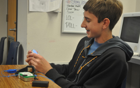 Freshman Alex Jones sits back to admire his gadgets. Recently he made his own watch and iPod out of simple household materials.