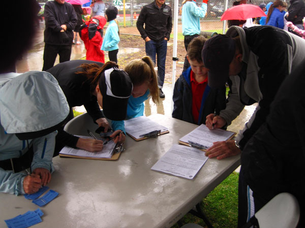 Despite the rainy conditions for the 2012 Mithcell Thorp Walkathon, a Carlsbad family registers the day of the event.  Walkers and runners at this year's event should expect a much sunnier forecast.