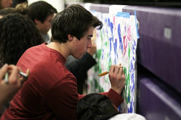 Senior Jacob Evans signs the poster promising to