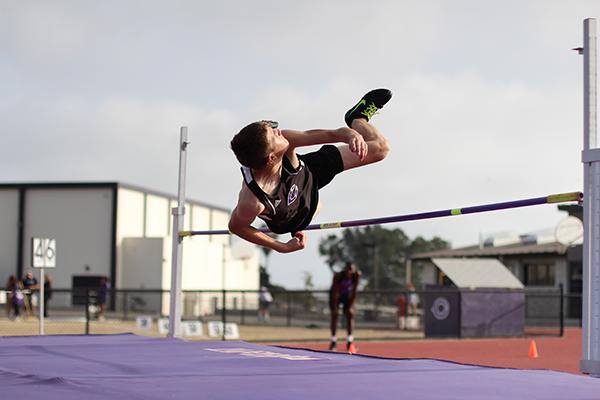 Junior Eithel Krauss jumps over the bar in the high jump competition at Thursday's track meet. He uses a technique different than the typical