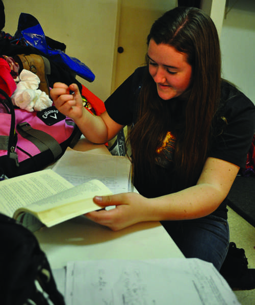 Junior Alendria O'Connor takes time during her dress rehearsal to catch up on homework. Many performers feel stressed during show performances and rehearsals are the perfect time to relax and catch up on extra work.