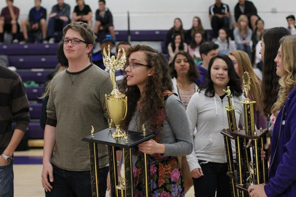 Senior Natalia Phillips holds Speech and Debates trophy during the assembly.