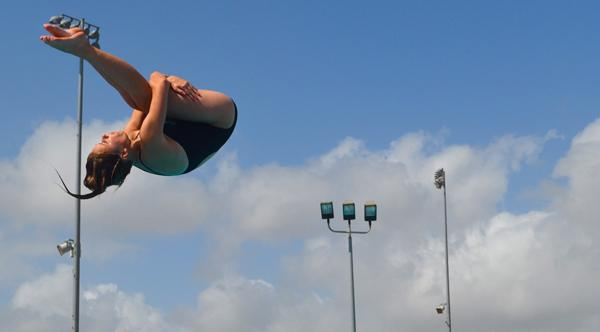 Varsity diver and senior Emma Rudolph practices her back flip at after school practice. Practice every day consist of activities on land and in the water.water