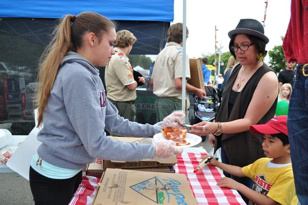 Junior Coco Monaco volunteers her time at the Carlsbad street fair. Coco, a member of the Key club at CHS, worked to sell slices of pizza to raise money for the club.