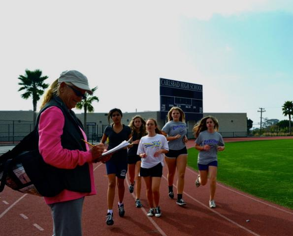 PE teacher Jane McGhee checks in students as they round the track during PE class. McGhee treated the campus to 40 dozen doughnut holes before school on Tuesday, Feb.5 to celebrate her 40th year of teaching.