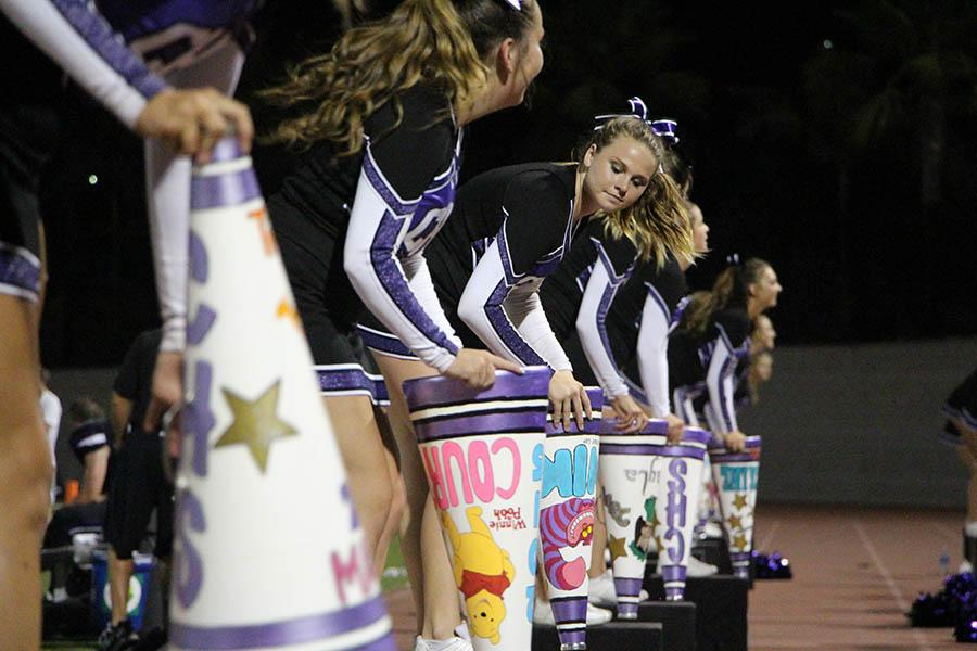 Varsity cheer members rally the crowd at the end of a Carlsbad win at the first home game against Great Oaks. The team practices two days a week so they can stay in top shape for their demanding routines and is present at all varsity football games to help pump up the crowd and players.