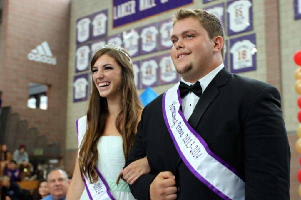 Homecoming princess Ashley Welzel and prince Vince Barone walk down the aisle during the Lancer Day assembly. These two seniors are thrilled to have the honor of being on homecoming court.