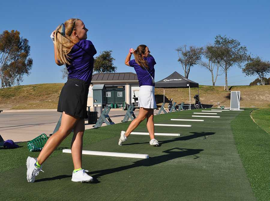 Seniors Brittany Bilek and Lauren Kirkwood devote time after school to practice their golf swings. Instead of having organized practices, the team is responsible for devoting time to improve personal technique .