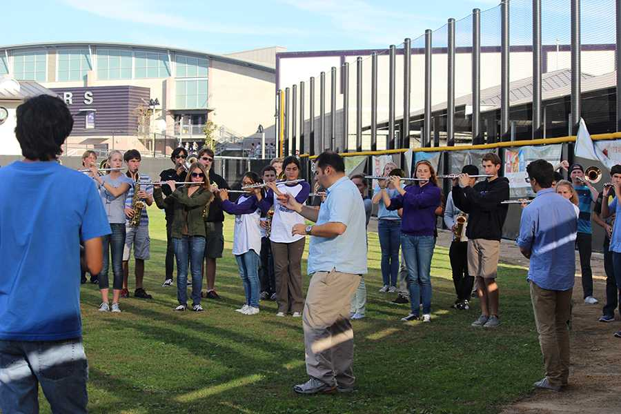 Mr. Bovie leads the band in a warm up tune at practice on the baseball field. The students in band are adjusting to the new director this year and are looking forward to winning future competitions.
