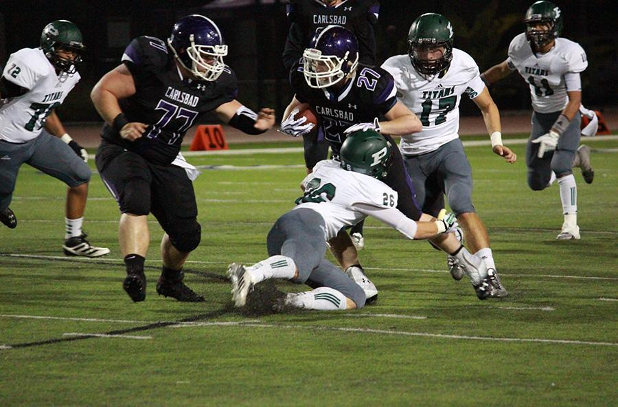 Junior Dylan Rutledge, protected by senior Vince Barone, makes a vital rush against the Poway Titans. Carlsbad came out with the win, and has proved yet again that the team is a force to be reckoned with going into the first game of CIF.
