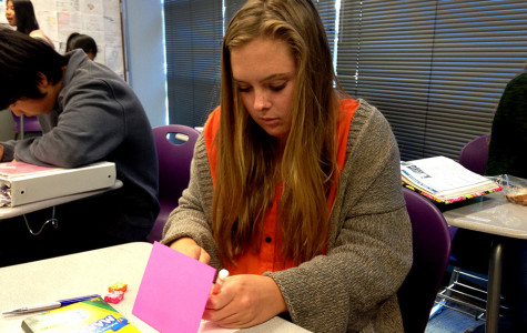 Junior Andrea Wagner  decorates a holiday card that will be given to a veteran. Red Cross Club participates in Holiday Mail for Heroes to brighten up the season for others.