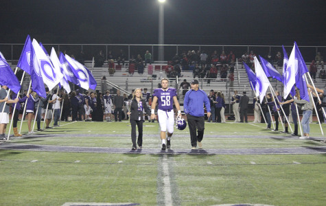 Damian Mirizzi is escorted by his mother and father on Senior Night, before the last home football game at Carlsbad of the 2013-14 regular season. Lancers came out on top over Vista with a 42-0 victory.