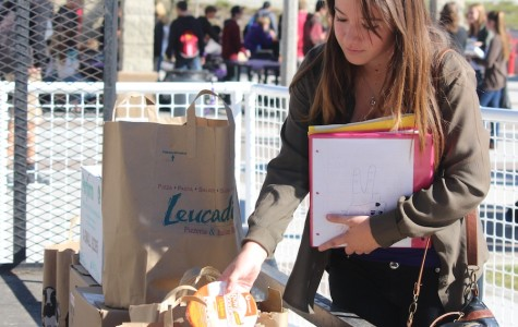 Senior Nicole Forth drops off non-perishable food for the Fillabus food drive during lunch in the quad.  Students were encouraged to donate anything they could and could even receive Lancer points for donating.