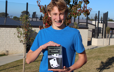 Justin Oetting holds his book