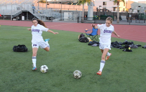 Freshman, Caitlin McCarthy (right) and Erin Sinai (left), practice their kicks before the Westview game. Both girls hold impactful positions on womens varsity soccer.
