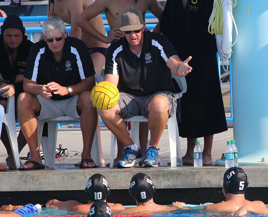 Coach Feaster has a half time pep talk with his team at a boys water polo game. Coach Feaster is one of many teachers who also coach in their free time.