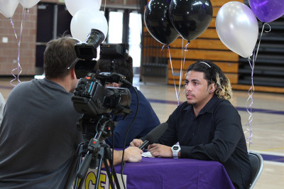 Senior Marcel McGrew gets interviewed shortly after his signing. Cameras continued to flash afterwards to capture the excitement of the players.
