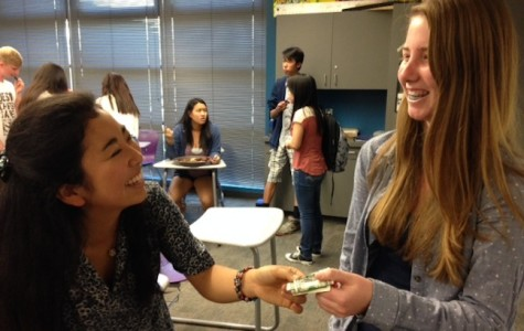 Club member, Kaylin Brennan, hands senior and president of Red Cross Club, Masami Amakawa, money collected for the Measles Initiative. Every year Red Cross Club participates in the Measles Initiative to raise money for less fortunate children who cannot afford to pay for measles vaccines.