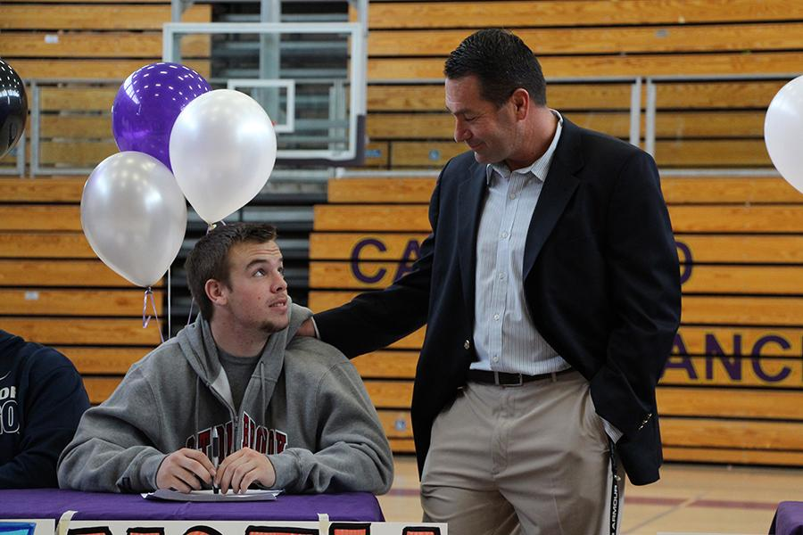Varsity Coach Mac Neal shares a moment with senior Noah McGinty shortly after the signing.