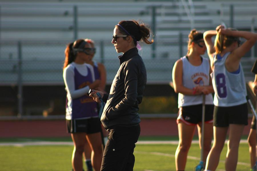 Coach Brooke Mihoces watches as members of the varsity girls lacrosse team practice for their upcoming games. Nihoces is being honored for her hard work and contributions to the girls team.