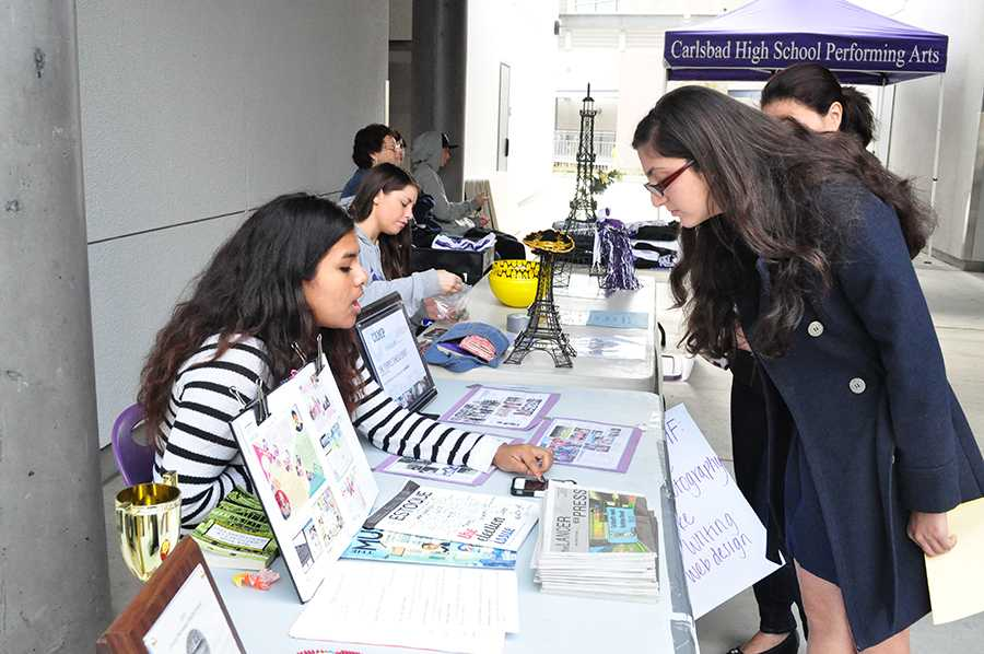 At freshman orientation, clubs and organizations set up booths to attract perspective members. A member of journalism talks to an eighth grader and her mom about joining the staff next year.