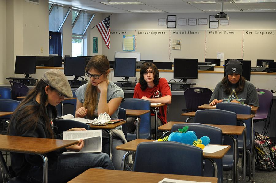 Members of the creative writing club flip through last years literary magazine to get ideas for this year. Submissions for the literary magazine are due by March 30 and all entries are welcome.