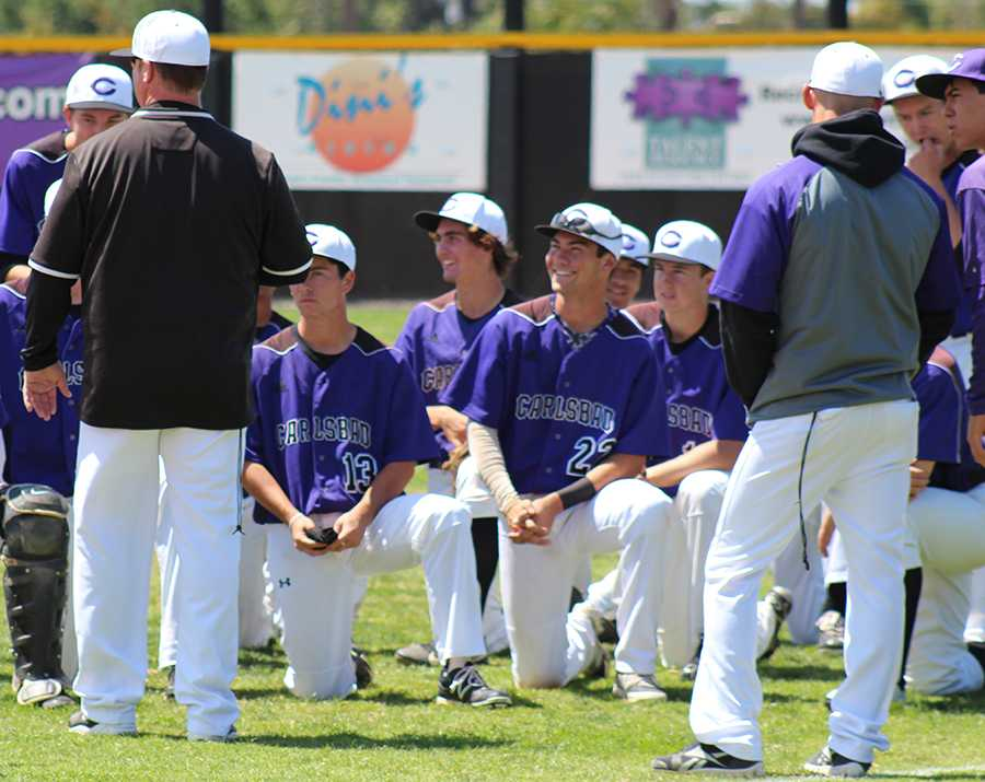 The varsity boys baseball team jokes with their coach after defeating the Warriors 5-1. Players spirits were high after the win, continuing the Lancers' winning record.