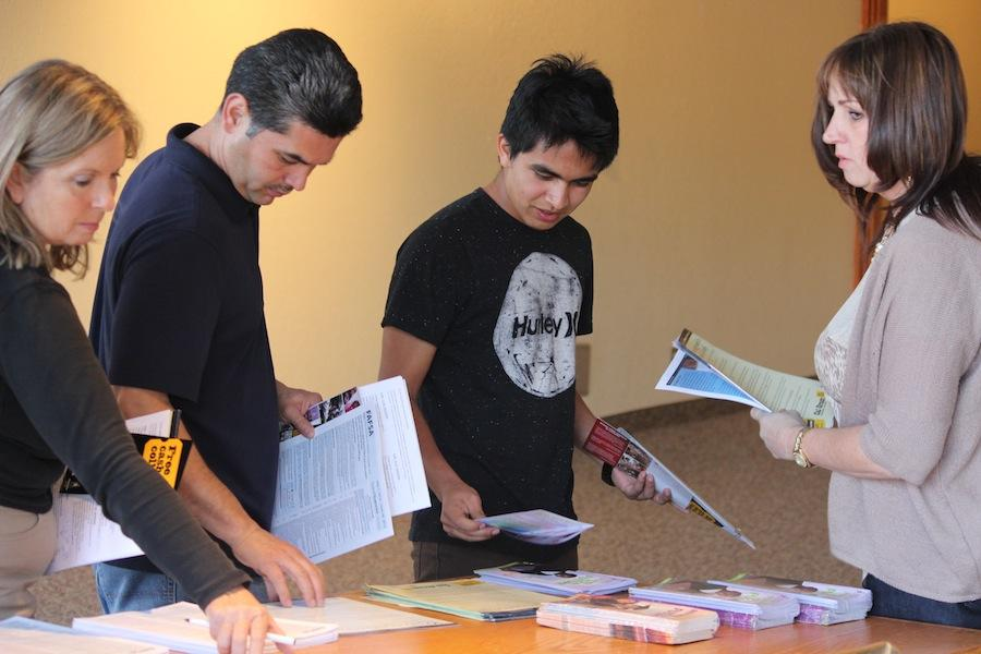 Junior+Adolfo+Amaya+picks+up+brochures+regarding+college+admissions+and+financial+aid++which+were+one+of+the+many+sessions+offered+to+juniors+and+sophomores+at+the+college+night+on+Wednesday%2C+April+16.++Both+parents+and+students+were+encouraged+to+attend+the+seminars+led+by+college+representatives.