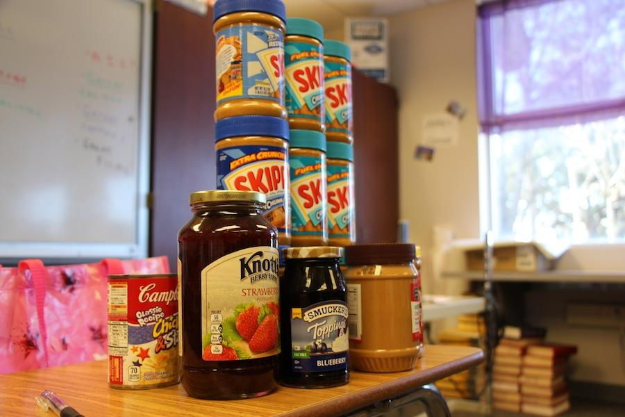 Peanut butter and jelly donations sit stacked on a table in room 3103, where Interact meets every odd Tuesday. As a part of their goal this year to help world hunger, Interact is collecting non-perishable foods.