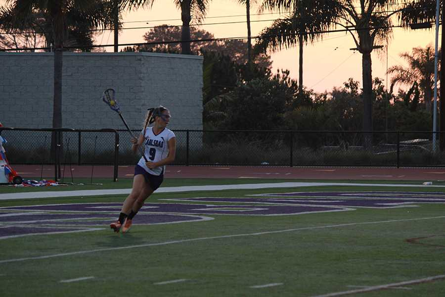 Sophomore Delaney Benson carries the ball behind the goal in hopes of finding a pass leading to a goal. The girls varsity team beat San Marcos in a hard fought game.