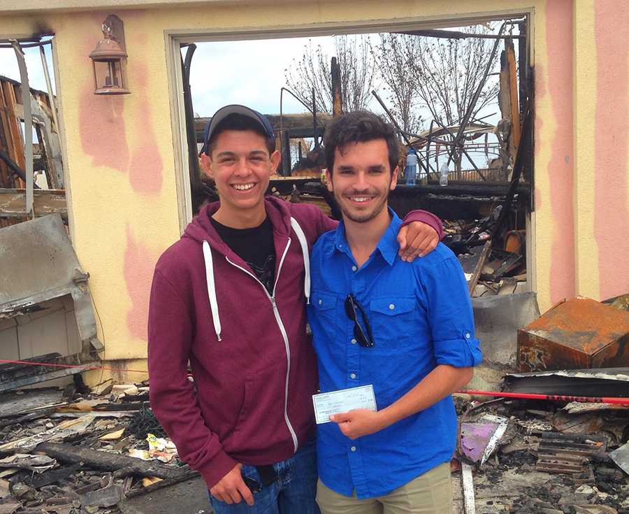 Seniors+Anthony+Castelli+and+Adam+Gilmore+stand+in+front+of+Gilmore%27s+burned+home+with+a+generous+donation+for+the+Gilmore+family.++The+Gilmores+lost+their+home+in+the+wildfire+that+burned+through+Carlsbad+on+May+14.