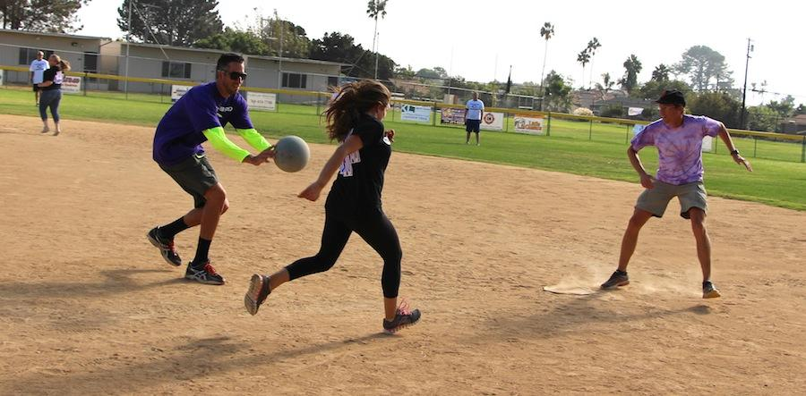Mr.Tomkinson runs to tag Senior Rebecca Nasser headed towards  first base in the staff vs. students kickball game on Monday, Oct.13.  Though both teams fought valiantly, the teachers came out with a hard-earned win.