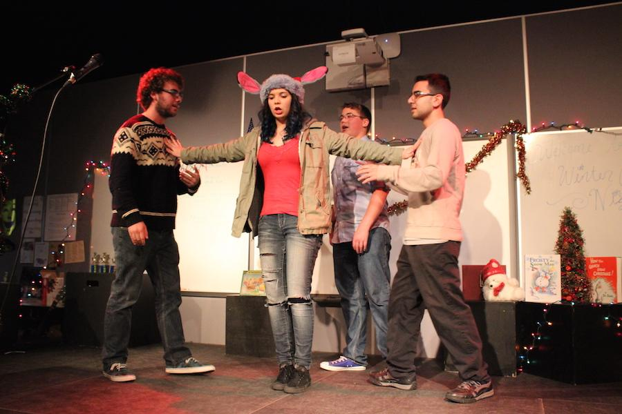 Members of improv club take the stage in a game during their holiday themed Coffee House Night. Many people brought food to contribute to the potluck and there was lots of audience participation as well.