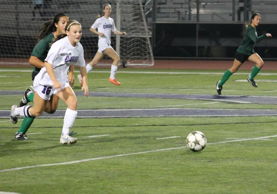 Senior Christina Nixon dribbles down the field. Nixon has been on varsity for three years.