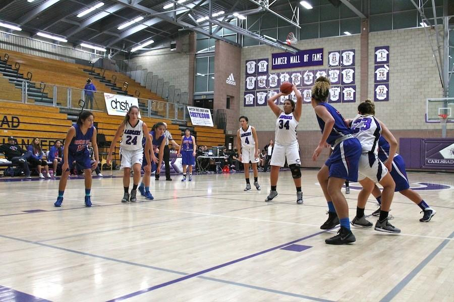 Junior Kimberley Wynn goes for a free throw shot against the opposing team. Lancers beat Orange Glen High School by a win of 63-8.