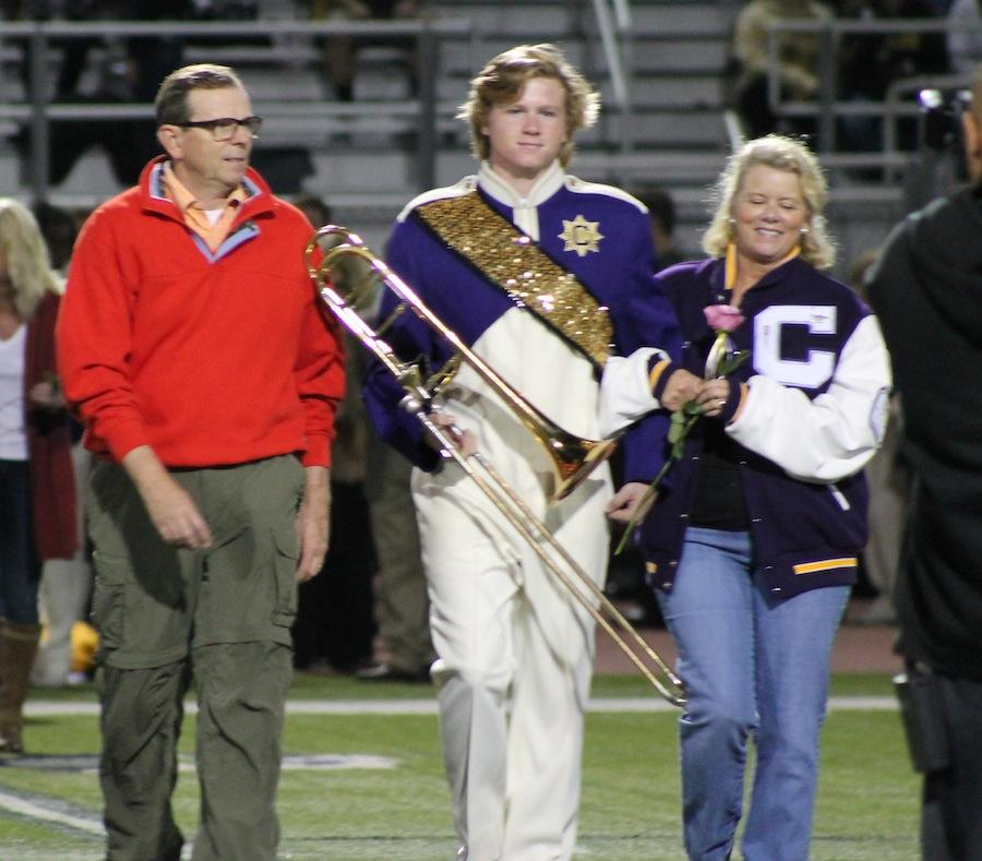 Senior+Dallin+Haslam+walks+onto+the+field+with+his+parents+on+senior+night+Oct.+30%2C2014.+Along+with+being+involved+in+band%2C+Haslam+participates+in+lacrosse.