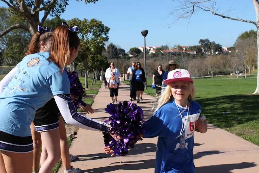 Carlsbad lancers cheerleaders cheer on runners during the Mitchell Thorp walkathon. This is the fifth year that they have had the Mitchell Thorp walkathon.