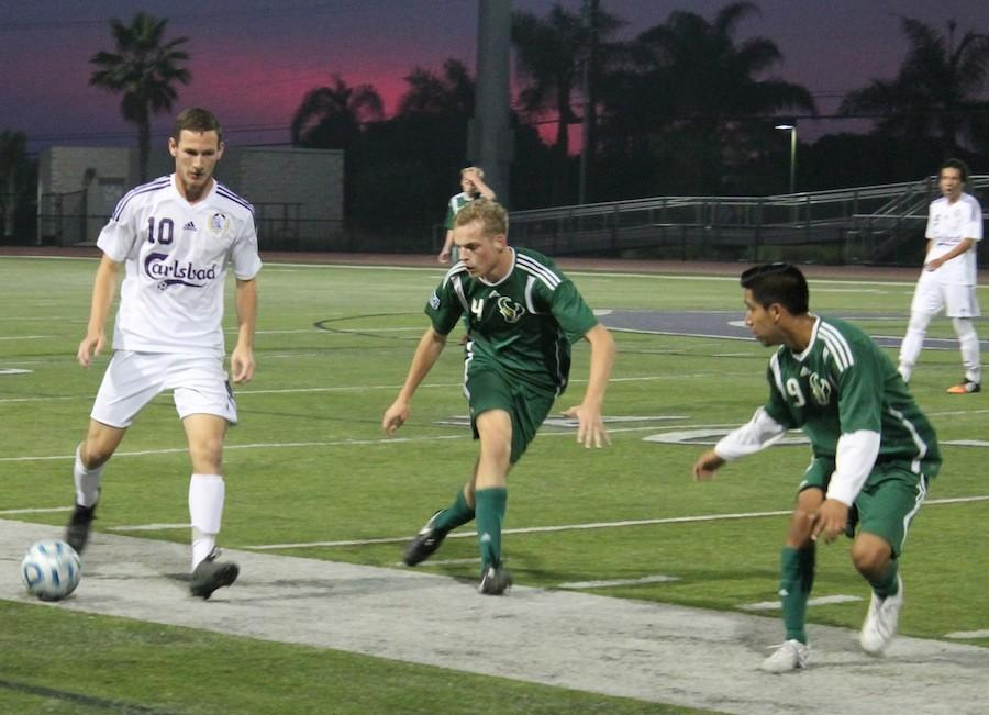 Senior Ryan Brent plays the ball past two LCC defenders. Carlsbad played LCC for their senior night and tied 0-0.