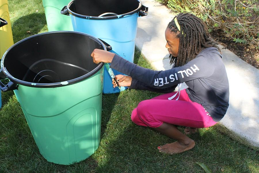 Eighth grader, Adokor Swaniker, helps paint a recycle bin for the recycling program starting at Valley Middle School this year. In this program students are able to make a direct impact on the betterment of their school.