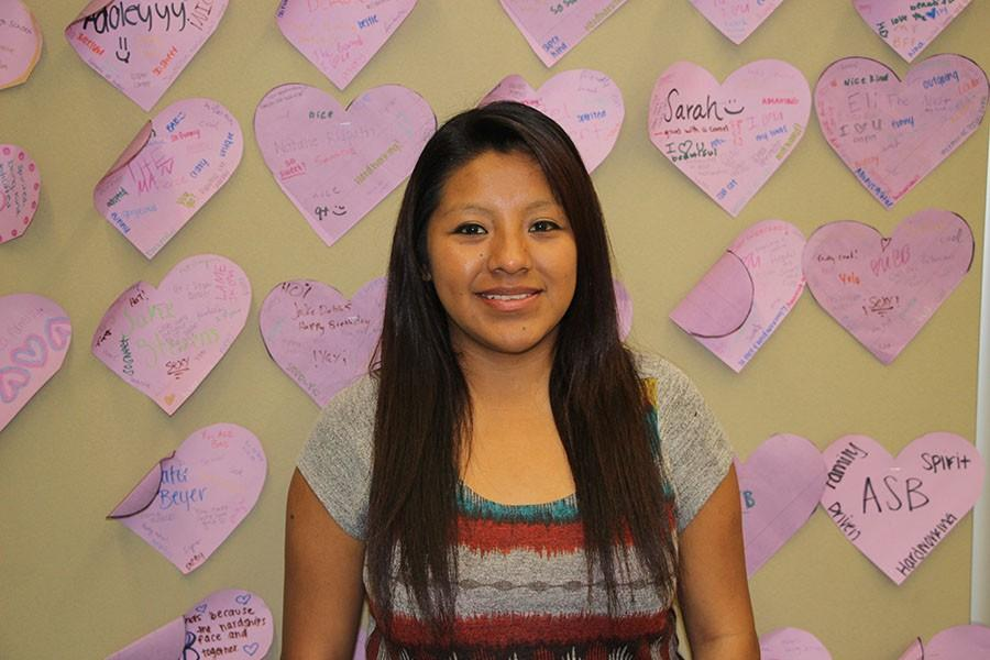 Lesly  Morella poses in front of a wall of hearts in the ASB classroom where kind notes to fellow classmates are posted. Lesly participates in the various class activities alongside her peers.