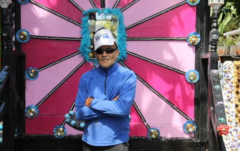 The artist, Richard Margolin, stands in front of his main centerpiece. Some recurring themes in his work include the use of bright colors and faces to give his art the liveliness it needs.