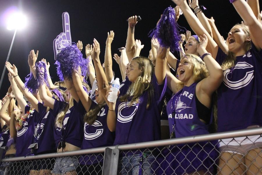 Loud crowd members, decked out in purple attire, cheer on the Lancers.
