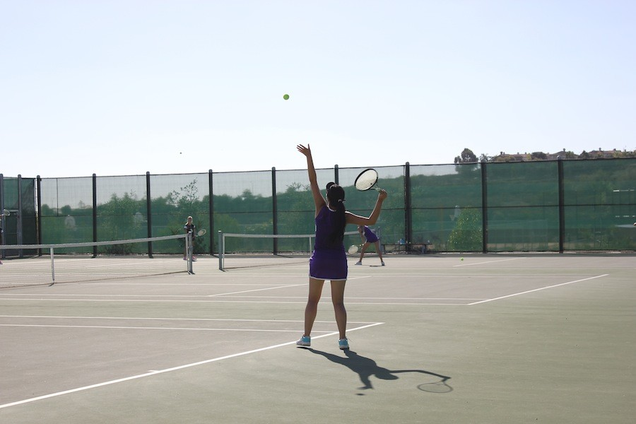 Varsity girls tennis play against Sage Creek.  Erica Zeng serves the ball, ending in a point for Carlsbad.