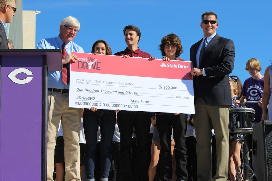 Tuesday, December 8, Carlsbad seniors, Sydney Payne, Joey Szalkiewicz, and Nick Lamarca from broadcasting, accept the check for $100,000 from the Celebrate My drive contest.